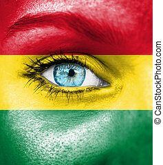 Woman face painted with flag of Bolivia