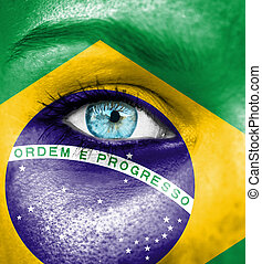 Woman face painted with flag of Brazil