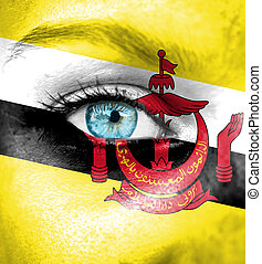 Woman face painted with flag of Brunei
