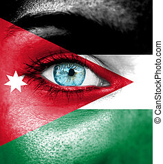 Woman face painted with flag of Jordan