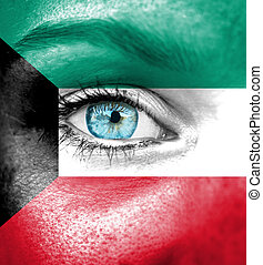 Woman face painted with flag of Kuwait