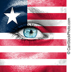 Woman face painted with flag of Liberia