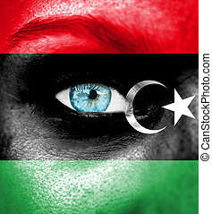 Woman face painted with flag of Libya
