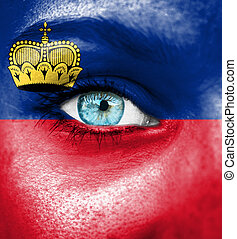 Woman face painted with flag of Lichtenstein