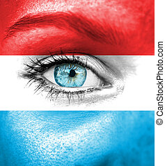 Woman face painted with flag of Luxembourg