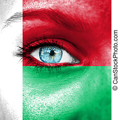 Woman face painted with flag of Madagascar
