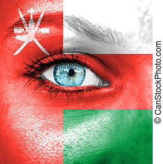 Woman face painted with flag of Oman