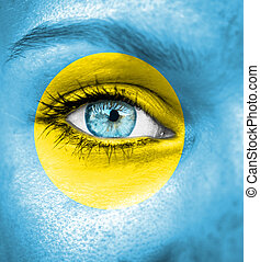 Woman face painted with flag of Palau