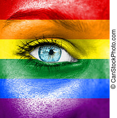 Woman face painted with flag of Pride