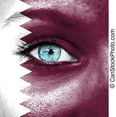Woman face painted with flag of Qatar