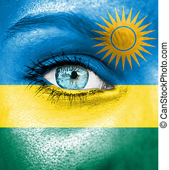 Woman face painted with flag of Rwanda