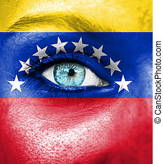 Woman face painted with flag of Venezuela