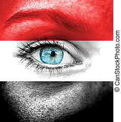 Woman face painted with flag of Yemen