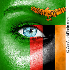 Woman face painted with flag of Zambia