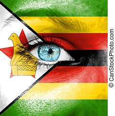 Woman face painted with flag of Zimbabwe