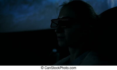 Woman face with 3d glasses looking around in movie theater...