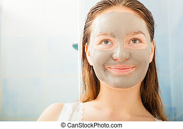 Woman face with mud facial mask