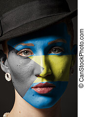 Woman face with painted Bahamas flag