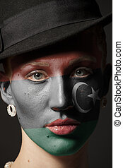 Woman face with painted Flag of Libya