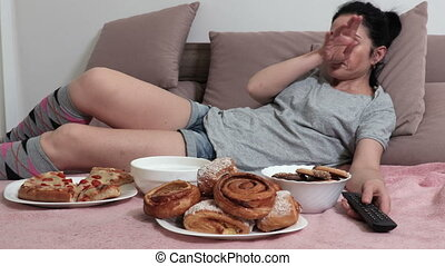 Woman fall asleep on bed after eating unhealthy food