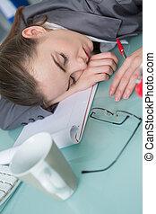 Woman fallen asleep at her desk