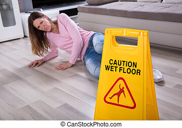 Woman Falling Near Caution Sign At Home