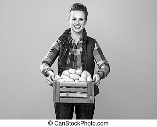 woman farmer isolated on yellow background with box of potatoes