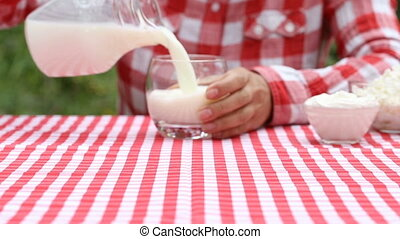 Woman farmer pours milk into glass from jug and holds it out