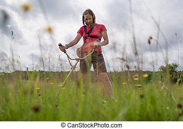 Woman farmer with a petrol trimmer mows the grass in the backyard of the village. Life in the countryside. Bottom view.