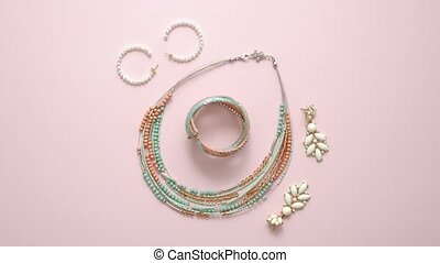 Woman fashion accessories. Jewelry. Earings, bracelet and necklace on stylish pastel pink background. Flat lay. Top view.