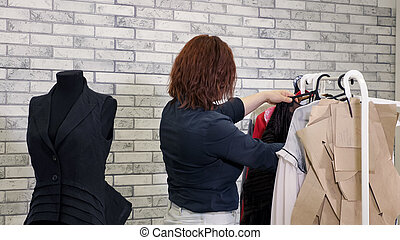 Woman fashion designer in workshop chooses clothes hang on hangers in atelier.