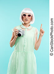 Woman fashion photographer with photo camera pointing up