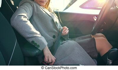 Woman fastening car safety seat belt while sitting inside of...