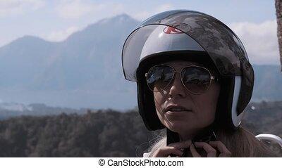 Woman fastening helmet over beautiful mountains landscape ...