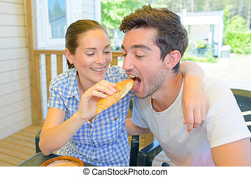 Woman feeding a croissant to her partner