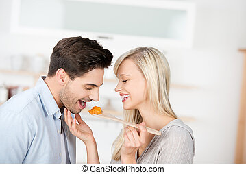 Woman Feeding Food To Man In Kitchen - Happy mid adult woman...