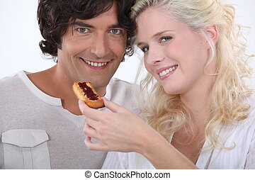 Woman feeding her boyfriend a biscuit