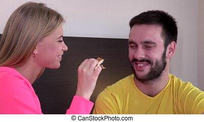 Woman feeding her boyfriend girl feeds from hands, closeup
