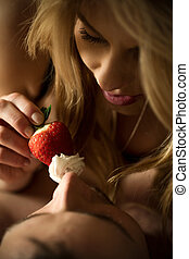 Woman feeding her lover with strawberry and cream