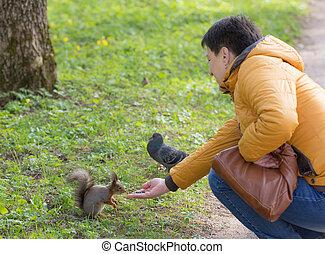woman feeds a squirrel