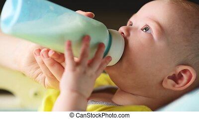Woman feeds her baby milk from a bottle