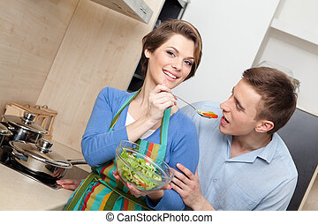 Woman feeds her husband with salad