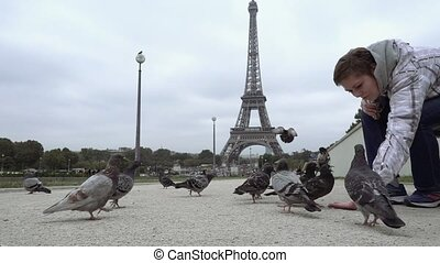 Woman feeds pigeons against Eiffel Tower