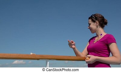 Woman feeds several gulls by bread and laugh at sunny day