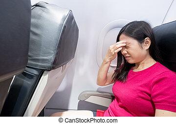 woman feel headache in airplane