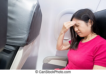 woman feel headache in airplane