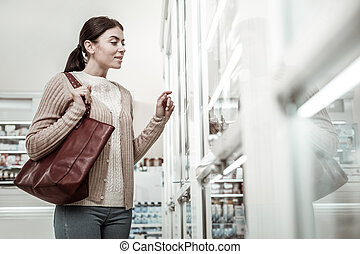 Woman feeling curious while choosing some cosmetics in pharmacy store