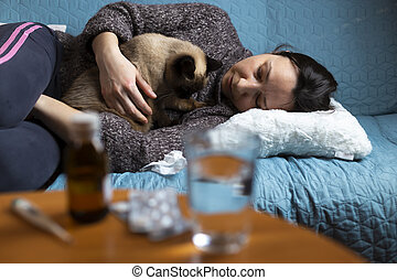 Woman feeling sick sitting on couch with her cat in her arms