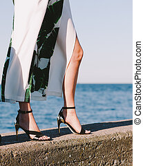 Woman feet wearing fashionable high heels summer shoes. Female walking on seaside pier next to sea water.