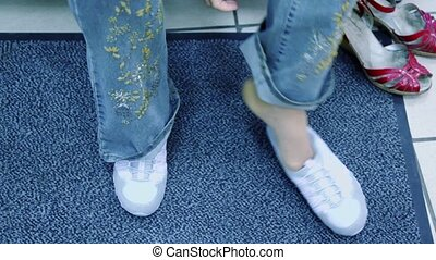 Woman feet in new shoes and old pair stand near on carpet
